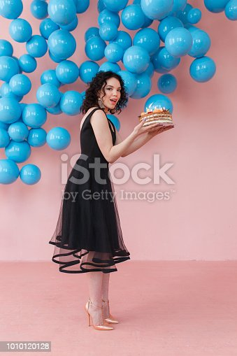 istock young girl holding birthday cake with candles in pink studio room with shiny blue balls decor 1010120128