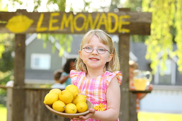 Young girl holding bowl of lemons in front of lemonade stand Young girl in front of lemonade stand holding lemons lemonade stand stock pictures, royalty-free photos & images
