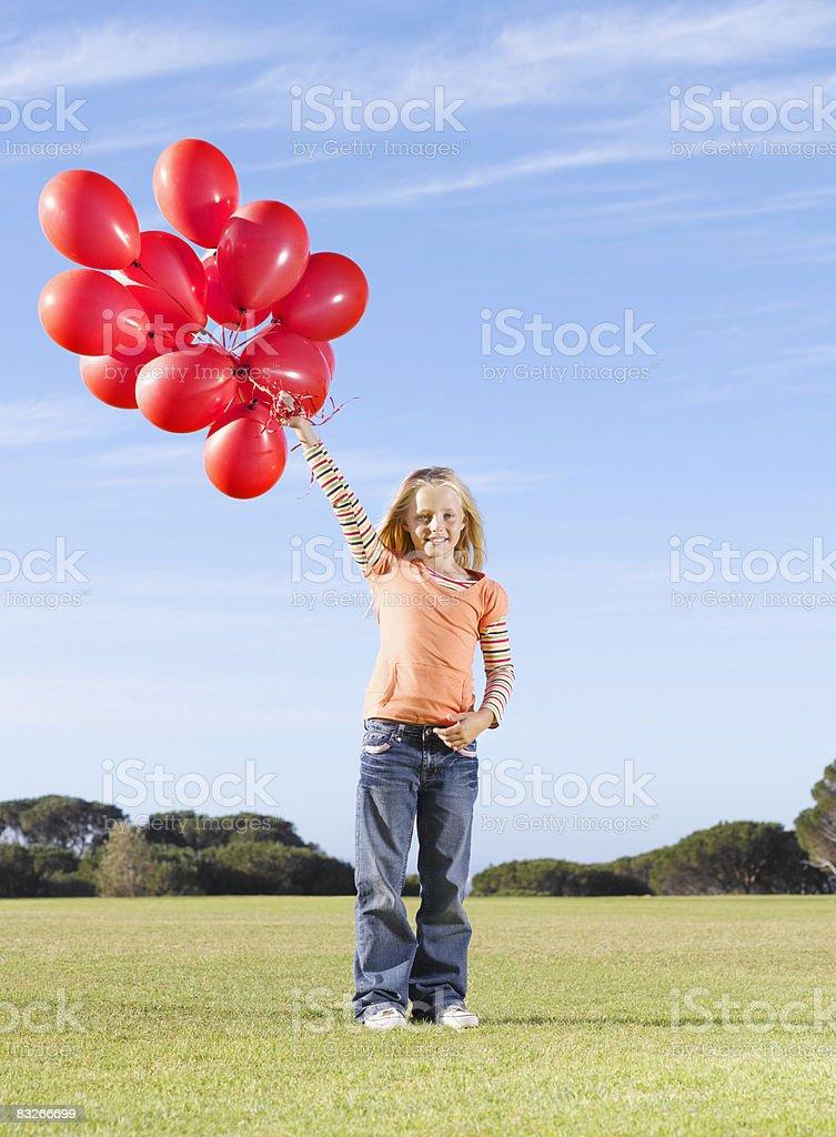 Junges Mädchen holding Bündel von red Ballons Lizenzfreies stock-foto