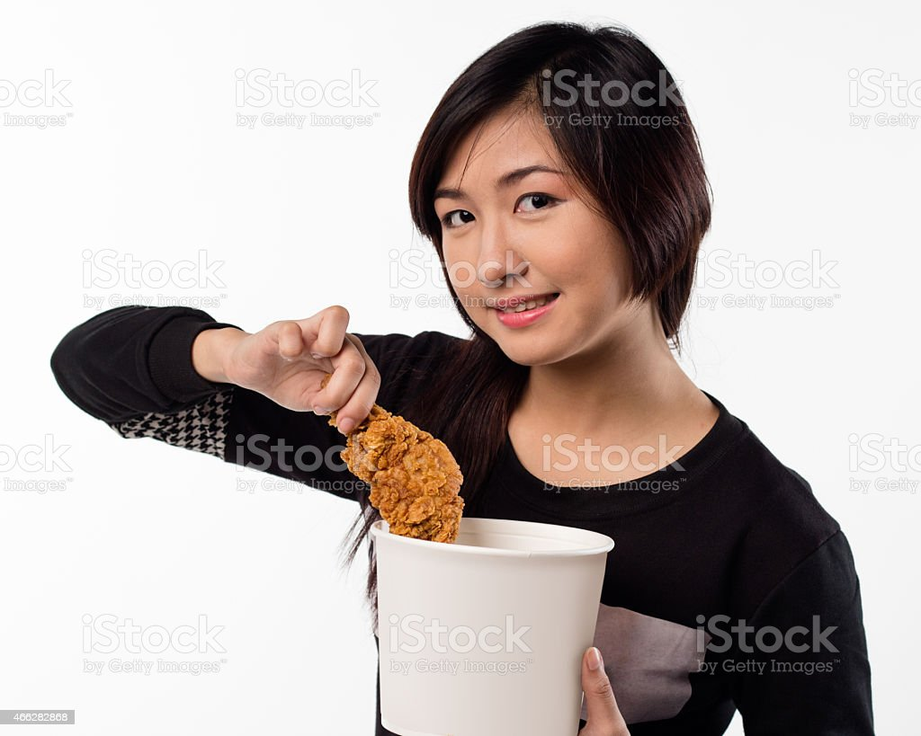 young girl holding, eating fried chicken stock photo