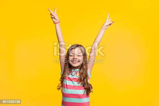 Young smiling girl wearing striped dress holding hands up with two fingers looking at camera.