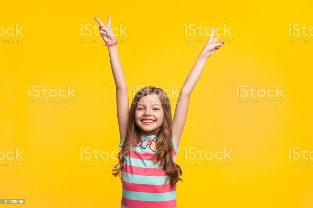 Young girl holding hands up smiling – zdjęcie