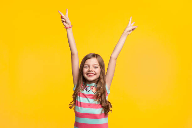 Young girl holding hands up smiling stock photo