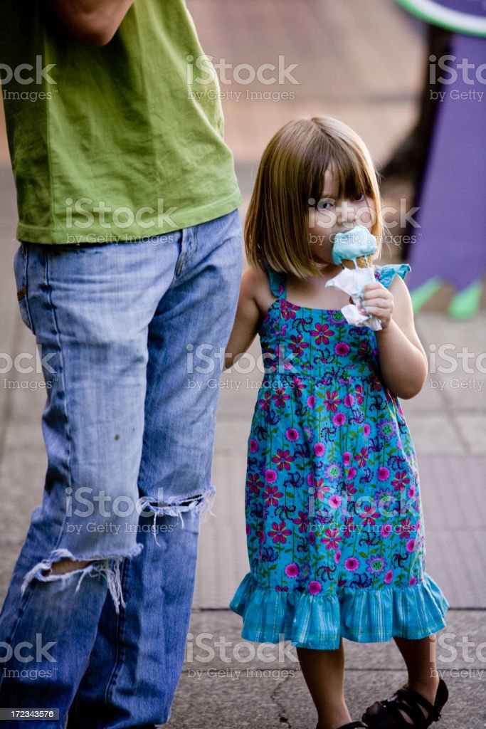 A young girl holding her parents hand and eating ice cream stock photo