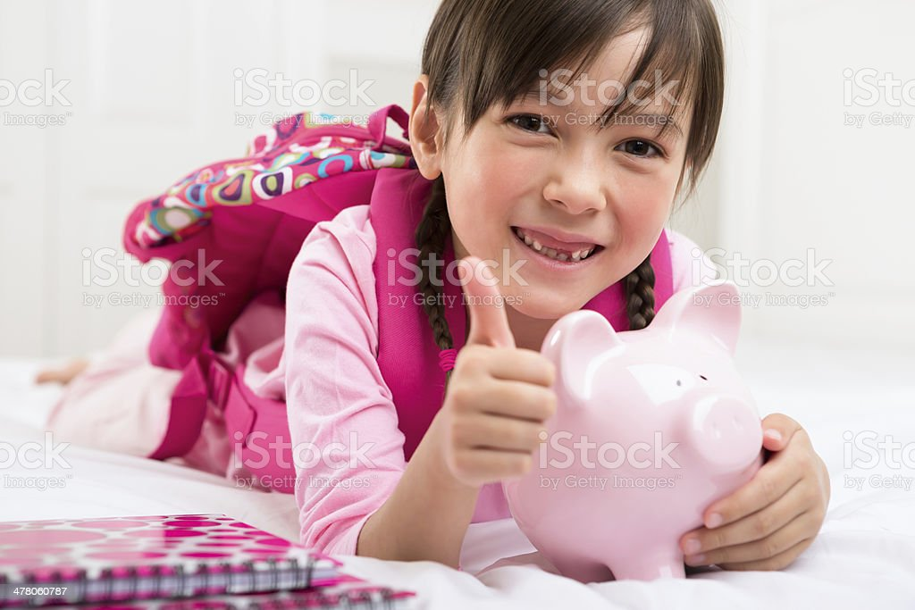 Young girl holding her piggy bank, giving thumbs up stock photo