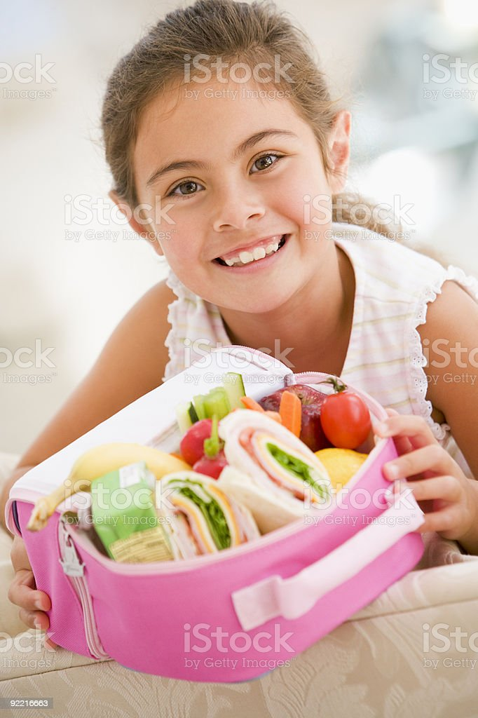 Young girl holding packed lunch stock photo