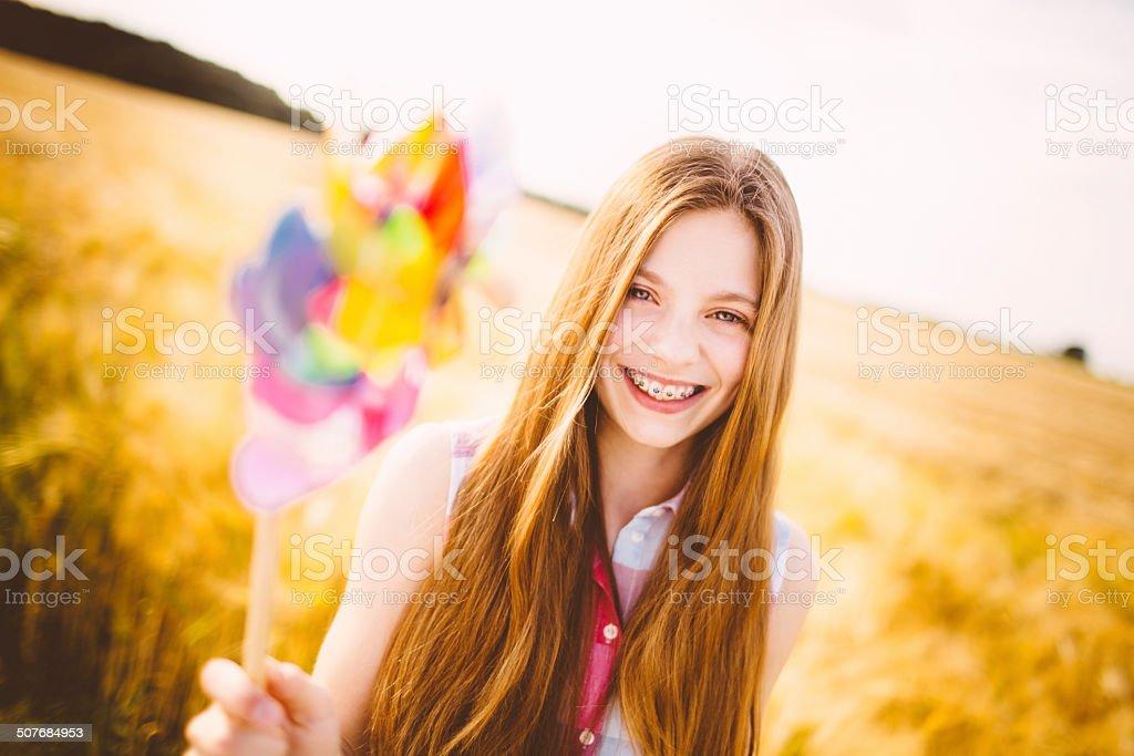 Young Girl Holding Pinwheel To Camera stock photo