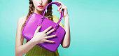 Young girl holding purple leather handbag purse. isolated on bright aqua blue background. Fashion item image.