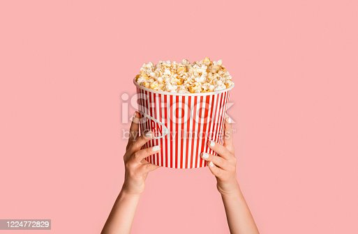 Young girl holding striped bucket with popcorn on pink background, close up view