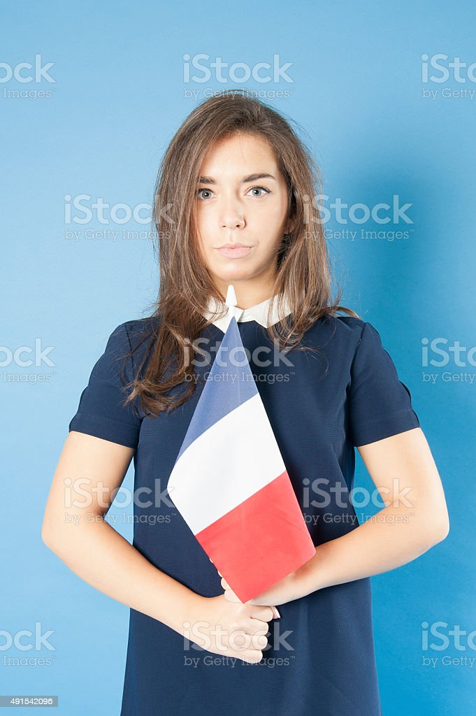 Young girl holding the French flag triumphantly. stock photo