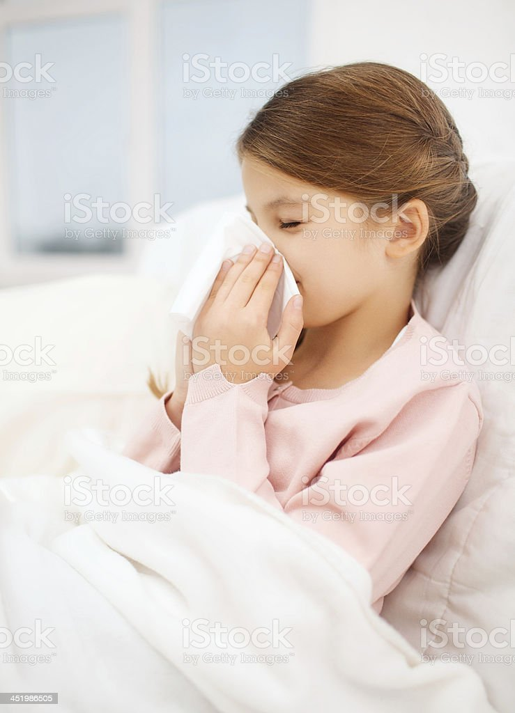 Young girl holding tissue to her nose stock photo
