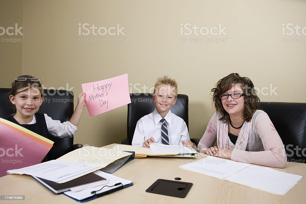 Young Girl Holds Mother's Day Sign at a Business Meeting royalty-free stock photo