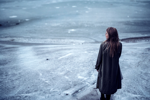 Young Girl how Standing Alone on Frozen Lake. Wearing glasses and winter coat outdoor on the snow frost.