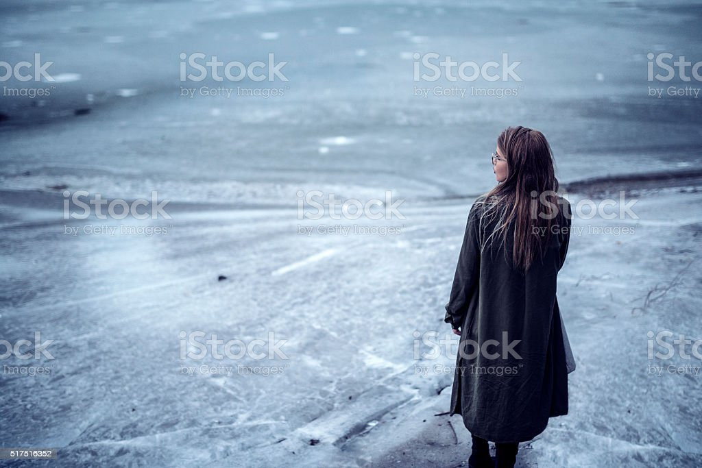 Young Girl how Standing Alone on Frozen Lake in Winter stock photo