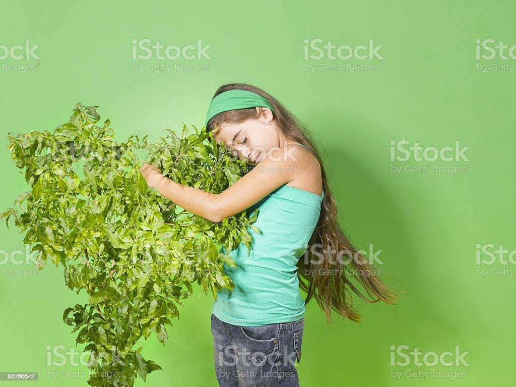 Young girl hugging green bush royalty-free stock photo