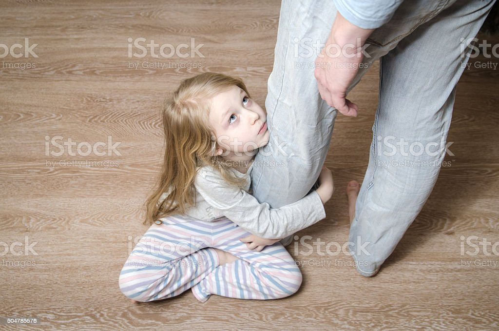 Young girl hugging her father's leg stock photo
