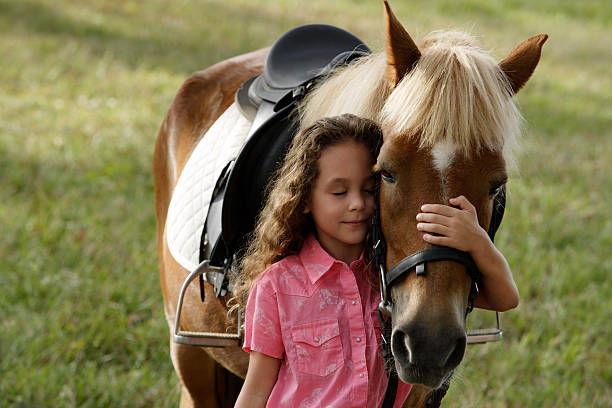 Young girl hugging nose of pony  pony stock pictures, royalty-free photos & images