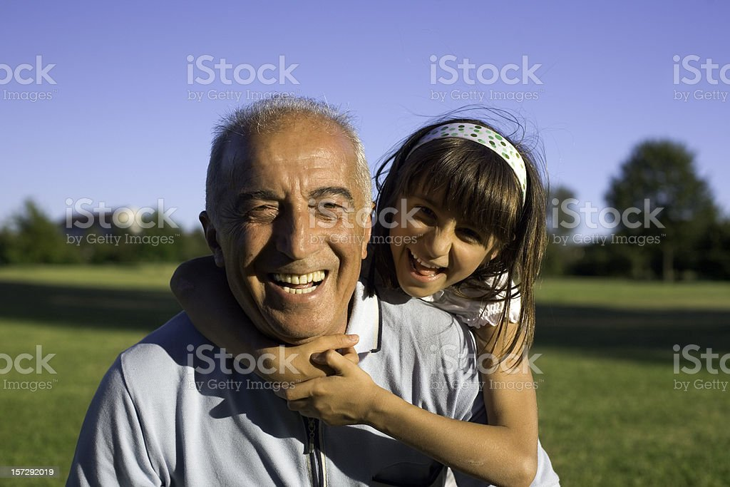 Young girl hugging older man during happy day at the park stock photo