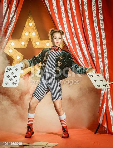 The nice young girl dressed in a magician costume shows the circus performance. The preadolescent girl is surprised looking at the camera. She is holding the large playing cards in her hands. Studio shooting on red background with glowing star and the striped theatrical curtain