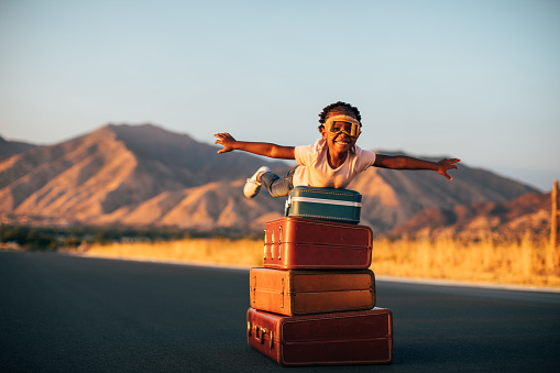 A young girl wearing flying goggles and has packed her suitcases and is ready to take a vacation even if it is imaginary. She is ready to fly away with arms outstretched to the destination of her dreams. Image taken in Utah, USA.