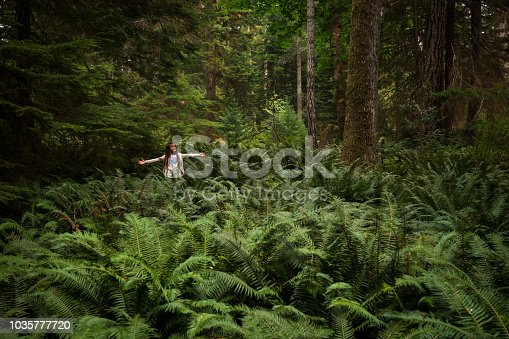 Child playing with a leaf in a lush green coastal forest