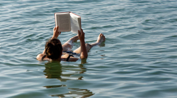 a young girl in a bikini lying motionless on her back in the dead sea reading a book. - morze martwe zdjęcia i obrazy z banku zdjęć