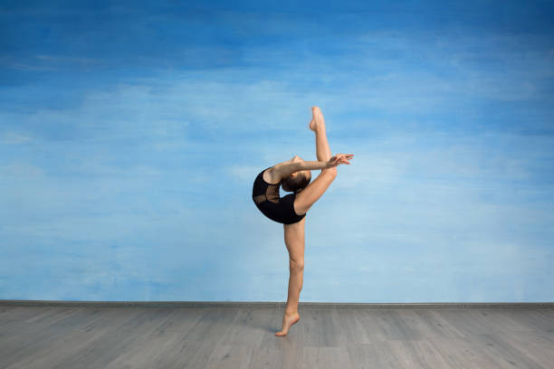 A young girl in a black gymnastic swimsuit gymnast makes an exercise standing backward and legs in semi splits on a blue background. A young girl gymnast performs kick back arms A young girl in a black gymnastic swimsuit gymnast makes an exercise standing backward and legs in semi splits on a blue background. A young girl gymnast performs kick back arms straightened back bending over backwards stock pictures, royalty-free photos & images