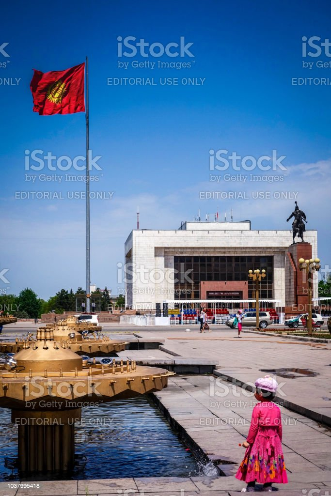 A young girl in a bright pink dress looks up at the Kyrgyz flag flying over Ala-Too Square, the main plaza in Bishkek. stock photo