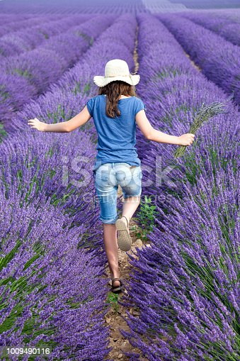 Young teen girl in a lavender fiel at full blossom, in Provence.