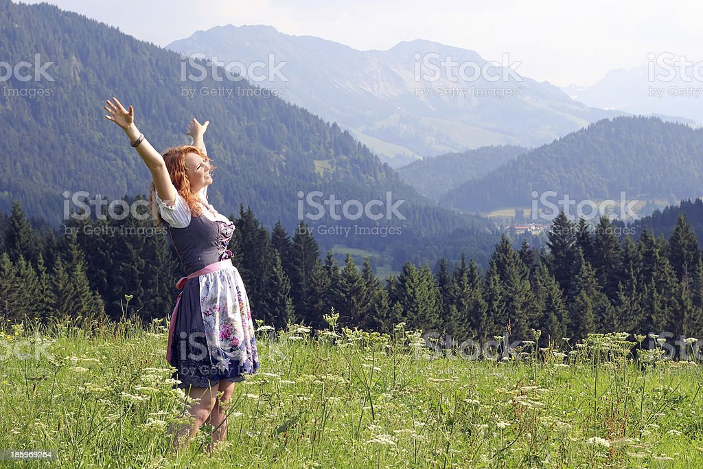 Young girl in a meadow wearing a dirndl stock photo
