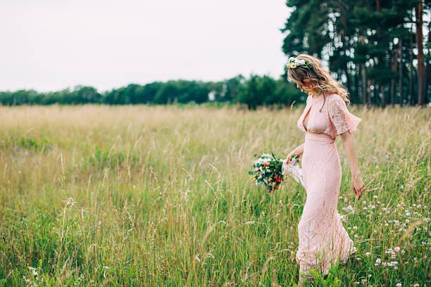young girl in a pink dress in the meadow - hochzeitsfrisur boho stock-fotos und bilder