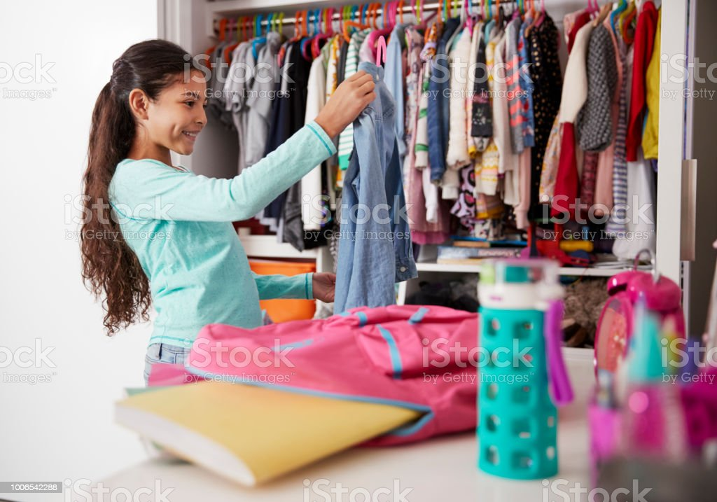 414ef9747bb0 Young Girl In Bedroom Choosing Clothes From Closet Stock Photo ...