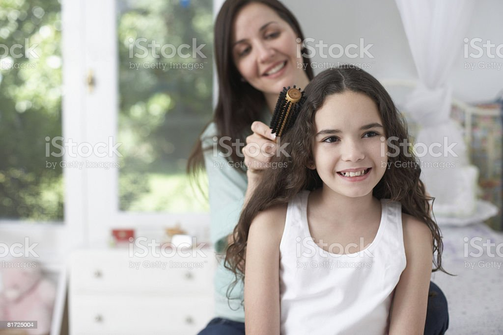 Young girl in bedroom having hair brushed by woman and smiling stock photo