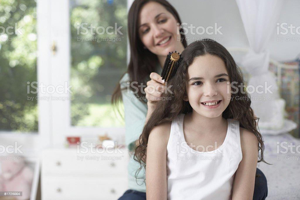 Garota no quarto depois de mulher com pincel no cabelo - foto de acervo