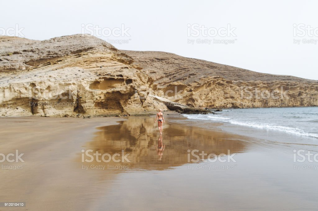 Young girl in bikini posing on sand beach in desert - fotografia de stock