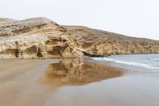 Young girl in bikini posing on sand beach in desert stock photo