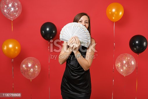 istock Young girl in black dress hiding, covering face with bundle lots of dollars, cash money in hand on bright red background air balloons. Women's Day Happy New Year birthday mockup holiday party concept. 1132755503