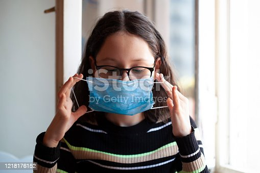 istock young girl in blue mask at home on corona days 1218176152