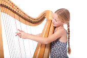 young girl in blue playing harp against white backgound