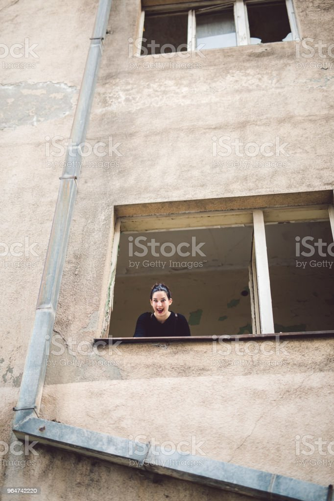 Young girl in broken window royalty-free stock photo