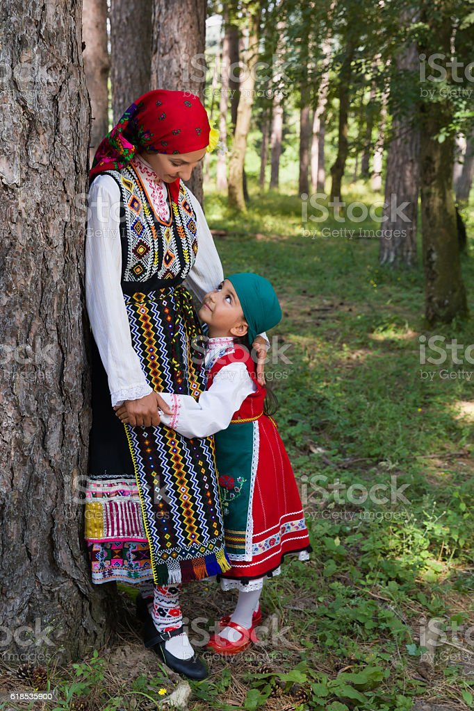 Young girl in Bulgarian dress posing with her Mother stock photo