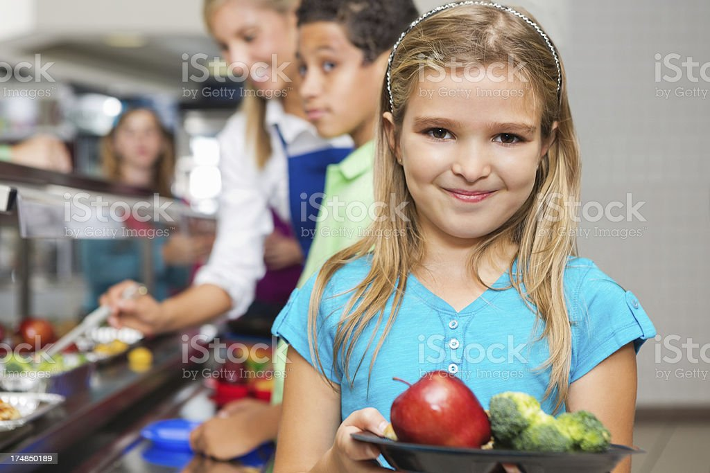 young girl in cafeteria line with fruits and vegetables royalty-free stock photo