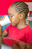 Afro american girls with corn rows in her hair is having a cup of water while her mother looks on.  RM