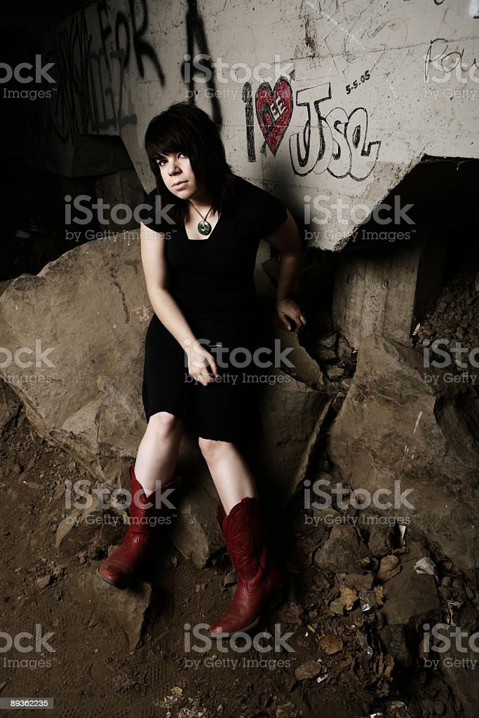 Young Girl in Dress and Boots Under a Bridge stock photo