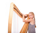 young girl in dress and her harp in studio against white background