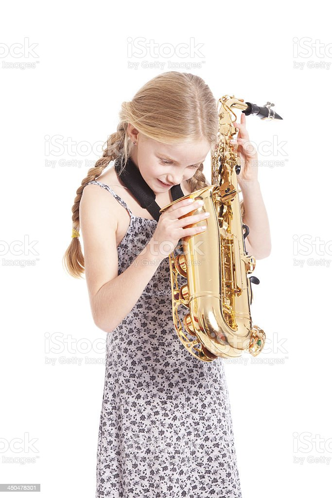 young girl in dress looking into saxophone royalty-free stock photo