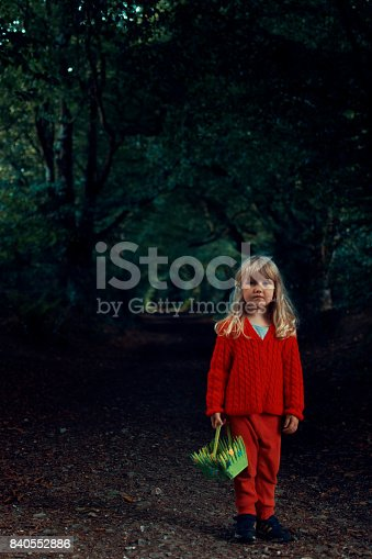 A young child (3 years old) out foraging in a dark and mysterious forest