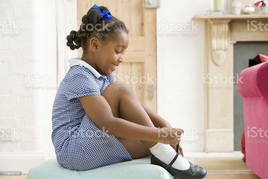 Young girl in front hallway fixing shoe stock photo