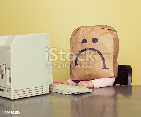 istock Young Girl in Front of Computer with Brown Bag Frown 499689350