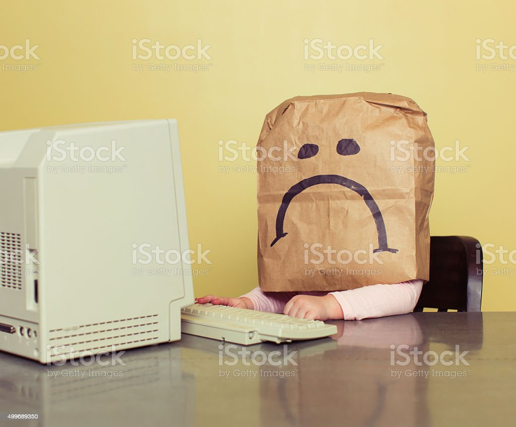 Young Girl in Front of Computer with Brown Bag Frown stock photo